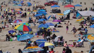 People enjoy the hot weather on Santa Monica Beach in Santa Monica, California, March 31, 2021. Half of the state's nearly 40 million people are now in the state's second-least restrictive orange tier amid low coronavirus case rates and increased vaccinations. Health officials in California and across the country are urging caution because of a troubling rise in new cases of COVID-19.