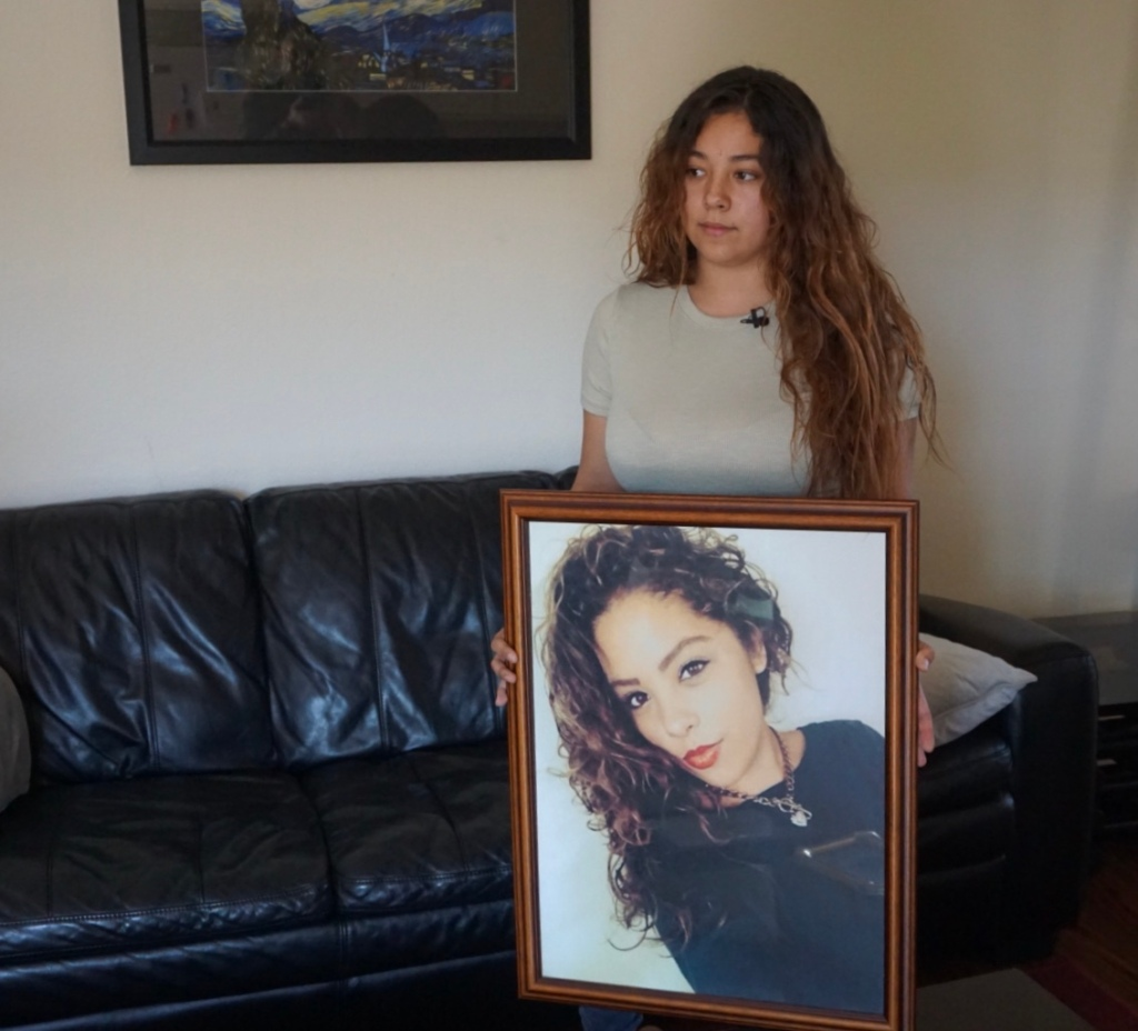 Clarissa Anderson holding a picture of her twin sister Chloe, who died by suicide. The family claims their private insurer did not make available adequate mental health services.