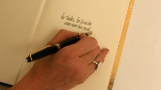 A person inscribes the first page of a book, 20 April 2006. SMG SPECTRUM Pictur
