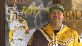 Man in a yellow hoodie and ballcap stands in front of a picture of Fernando Tatis, Jr.