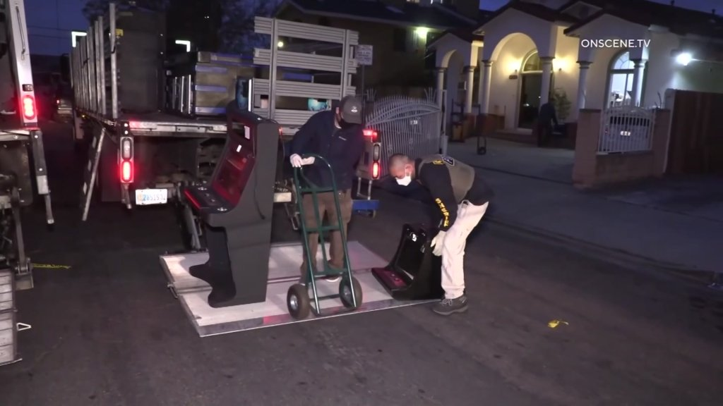 Federal authorities prepare to load a confiscated slot machine onto an evidence van on Wednesday, April 14, 2021.