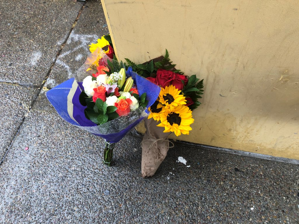 Flowers lean against the wall to the building where a man jumped and landed on top of a woman who was walking on the sidewalk below.