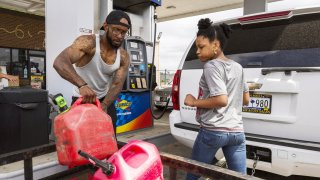 A man fills gas canisters with fuel at a Sunoco gas station in Sumter, South Carolina, on Tuesday, May 11, 2021.