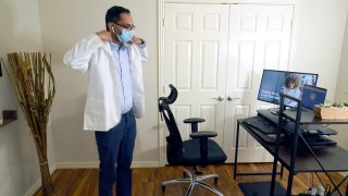 Medical director of Doctor on Demand Dr. Vibin Roy prepares to conduct an online visit with a patient from his work station at home