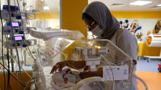 A Moroccan nurse takes care of one of the nine babies protected in an incubator at the maternity ward of the private clinic of Ain Borja in Casablanca, Morocco, Wednesday, May 5, 2021. A Malian woman gave birth to nine babies after n ' to have waited only seven, announced Wednesday the Ministry of Health of Mali. . Halima CissÈ, 25, gave birth by caesarean section Tuesday in Morocco after being sent there for special care, the ministry said.