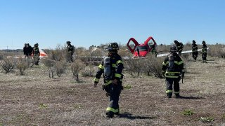 In this photo provided by South Metro Fire Rescue, emergency personnel work at the scene where a single engine plane landed after a mid-air collision near Denver, Wednesday, May 12, 2021. Federal officials say two airplanes collided but that there are no injuries. The collision between a twin-engine Fairchild Metroliner and a single-engine Cirrus SR22 happened as both planes were landing, according to the National Transportation Safety Board. Key Lime Air, which owns the Metroliner, says its aircraft sustained substantial damage to the tail section but that the pilot was able to land safely at Centennial Airport.