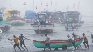 Fishermen try to move a fishing boat to a safer ground on the Arabian Sea coast in Mumbai, India, Monday, May 17, 2021. Cyclone Tauktae, roaring in the Arabian Sea was moving toward India's western coast on Monday as authorities tried to evacuate hundreds of thousands of people and suspended COVID-19 vaccinations in one state.