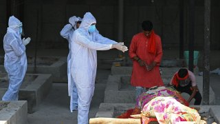 A family member wearing protective gear performs final rites on the funeral pyre of a Covid-19 coronavirus victim at a crematorium in New Delhi on May 24, 2021, as India passed more than 300,000 deaths from coronavirus pandemic.