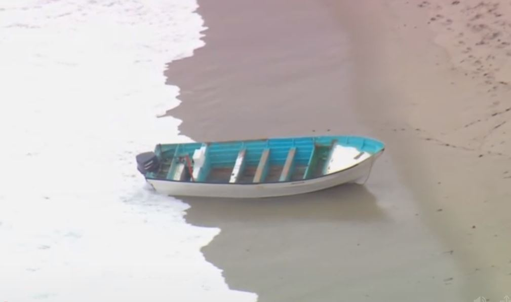 An empty boat, likely related to the human smuggling attempt, washes ashore on Thursday, May 20, 2021.