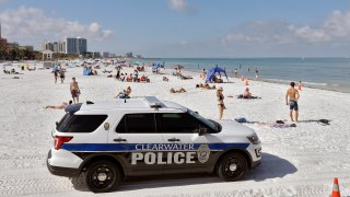 police officers patrol the area after Clearwater Beach officially reopened to the public in Clearwater Beach, Fla.