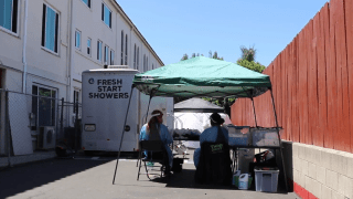 Think Dignity volunteers sit outside of Fresh Start Mobile Showers