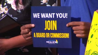 A sign is held encouraging San Diego youngsters to join the city's revived Youth Commission.