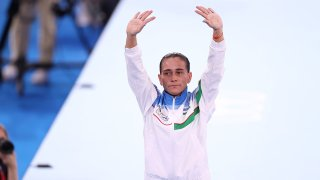 Eight-time Olympian Oksana Chusovitina waves after competing on vault at the Tokyo Olympics