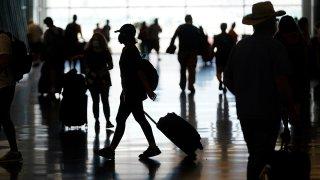 FILE - In this July 1, 2021, file photo, people travel through Salt Lake City International Airport in Salt Lake City.