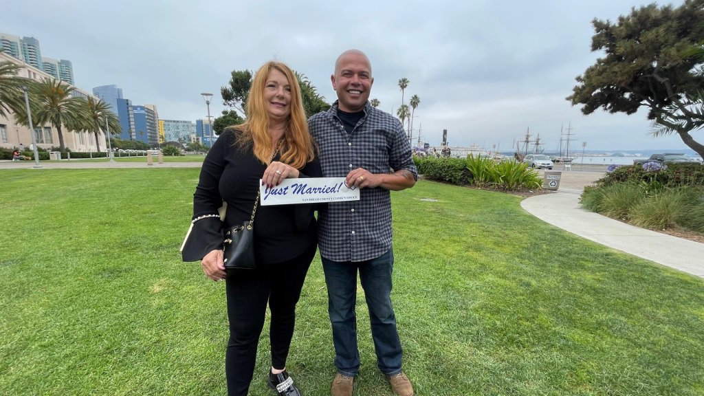 """A happy couple holds a """"Just Married"""" plaque after tying the knot at the Marriage Hut in San Diego. The Waterfront Park spot now offers couples marriage services with no appointments needed every Wednesday."""