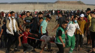 Medics evacuate a wounded person from the fence of Gaza Strip border with Israel