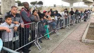 """FILE - In this Sept. 26, 2019, file photo asylum seekers in Tijuana, Mexico, listen to names being called from a waiting list to claim asylum at a border crossing in San Diego. The Supreme Court has ordered the reinstatement of the """"Remain in Mexico"""" policy, saying that the Biden administration likely violated federal law by trying to end the Trump-era program that forces people to wait in Mexico while seeking asylum in the U.S. The decision immediately raised questions about what comes next for the future of the policy, also known as the Migrant Protection Protocols."""