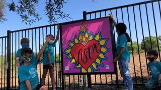 Children from the Boys & Girls Club of Vista pose with a painting featuring the city's name.