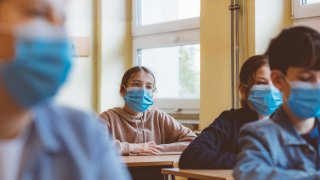 Students sitting and wearing a face mask in class.