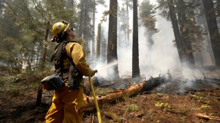 San Jose firefighter Ryan Godoy uses a hose to extinguish hot spots while battling the Dixie Fire on August 12, 2021 near Westwood, California.