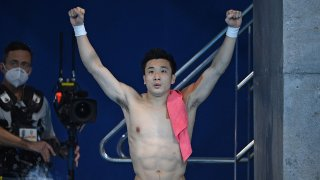 China's Cao Yuan celebrates winning the gold medal in the men's 10m platform diving event at the Tokyo Olympics.