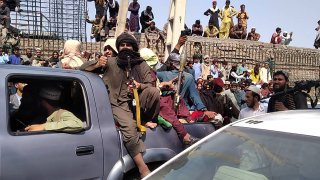 Taliban fighters sit on a vehicle along the street in Jalalabad province