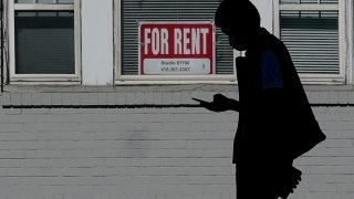 In this Oct. 20, 2020 file photo, a man walks in front of a For Rent sign in a window of a residential property in San Francisco