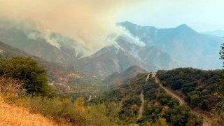 In this Sunday, Sept. 12, 2021 photo released by the KNP Complex Fire Incident Command, smoke plumes rise from the Paradise Fire in Sequoia National Park, Calif. In the southern Sierra Nevada, two fires ignited by lightning are burning in Sequoia National Park.