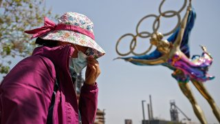 """FILE - In this May 2, 2021, file photo, a woman adjusts her face mask as she walks by a statue featuring the Beijing Winter Olympics figure skating on display at the Shougang Park in Beijing. China's """"zero tolerance"""" strategy of trying to isolate every case and stop transmission of the coronavirus has kept kept the country where the virus first was detected in late 2019 largely free of the disease."""