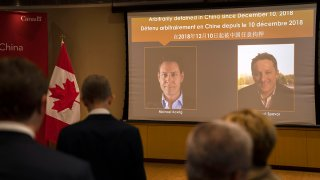 FILE - A video screen displays images of Canadians Michael Kovrig, left, and Michael Spavor at the Canadian Embassy in Beijing, Aug. 11, 2021. Kovrig and Spavor were released, along with Huawei executive Meng Wanzhou, in a three-way deal with China, Canada and the U.S., on Sept. 24, 2021.