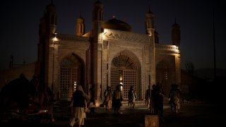 Taliban fighters walk at the entrance of the Eidgah Mosque after an explosion in Kabul, Afghanistan