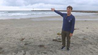 Man on beach pointing at ocean