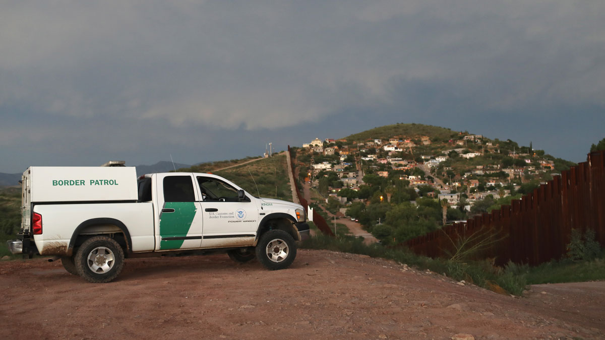 In this July 22, 2018, file photo, a U.S. Border Patrol agent watches over the U.S.-Mexico border at dusk in Nogales, Arizona.