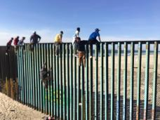 Stunning Images Show Migrant Caravan Atop Border Fence