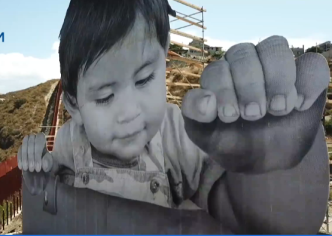 Artist Depicts Giant Baby Looking Over Border Wall in Mexico