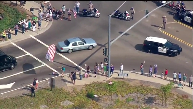 Citizens Wave Flags for Officer's Procession