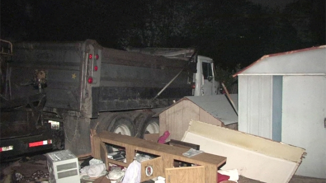 Dump Truck Smashes Through Fence, Into Parked Trailer