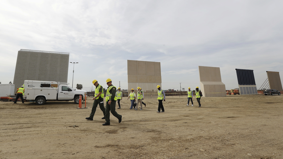 People pass border wall prototypes as they stand near the border with Tijuana, Mexico in San Diego. Companies are nearing an Oct. 26 deadline to finish building eight prototypes of President Donald Trump's proposed border wall with Mexico.