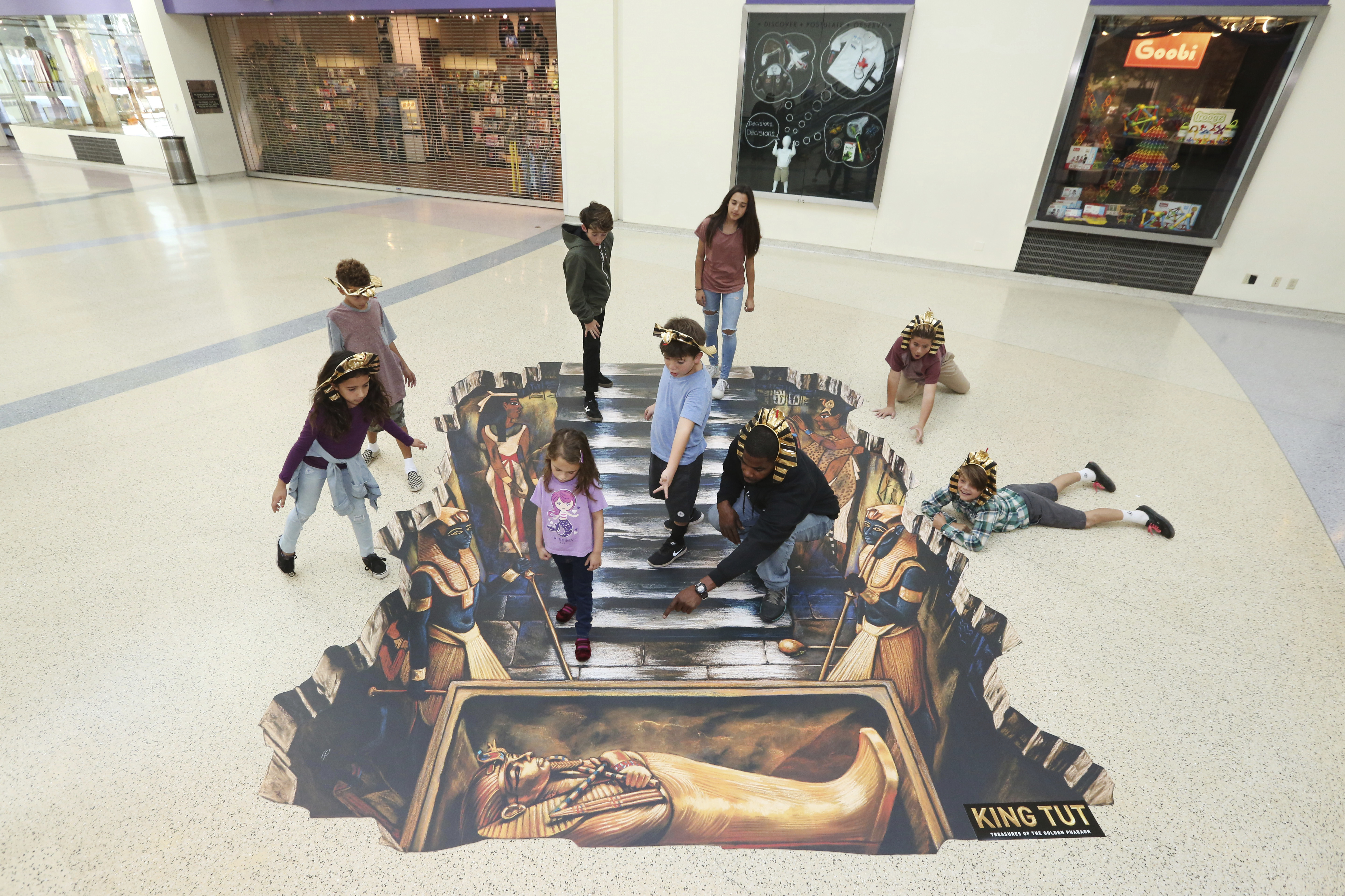 In this image distributed on Wednesday, Nov. 29, 2017, children celebrate the announcement of the KING TUT: Treasures of the Golden Pharaoh exhibition at the California Science Center in Los Angeles, overlooking an artistic recreation of his tomb that appears as if in 3D.