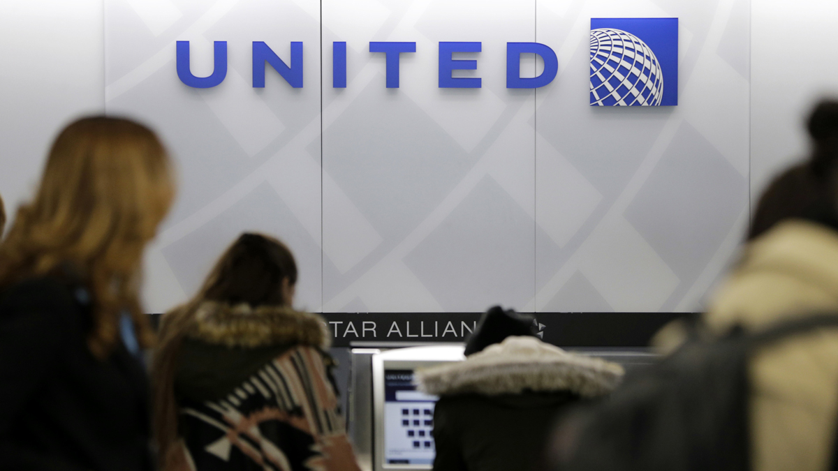 In this March 15, 2017, photo, people stand in line at a United Airlines counter at LaGuardia Airport in New York. A dog died on a United Airlines plane after a flight attendant ordered its owner to put the animal in the plane's overhead bin.