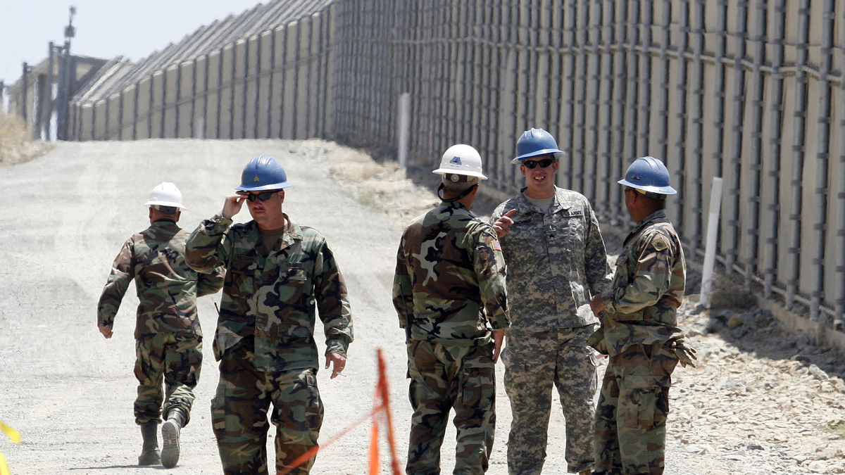 In this June 21, 2006, file photo, members of the California National Guard work next to the U.S.-Mexico border fence Wednesday, June 21, 2006, near the San Ysidro Port of Entry in San Diego. President Donald Trump said Tuesday, April 3, 2018, he wants to use the military to secure the U.S.-Mexico border until his promised border wall is built.