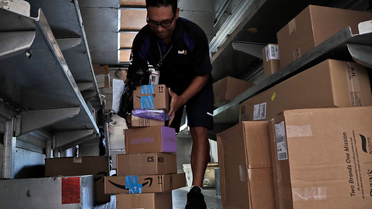 In this July 17, 2018, file photo, a FedEx employee delivers packages in Miami.