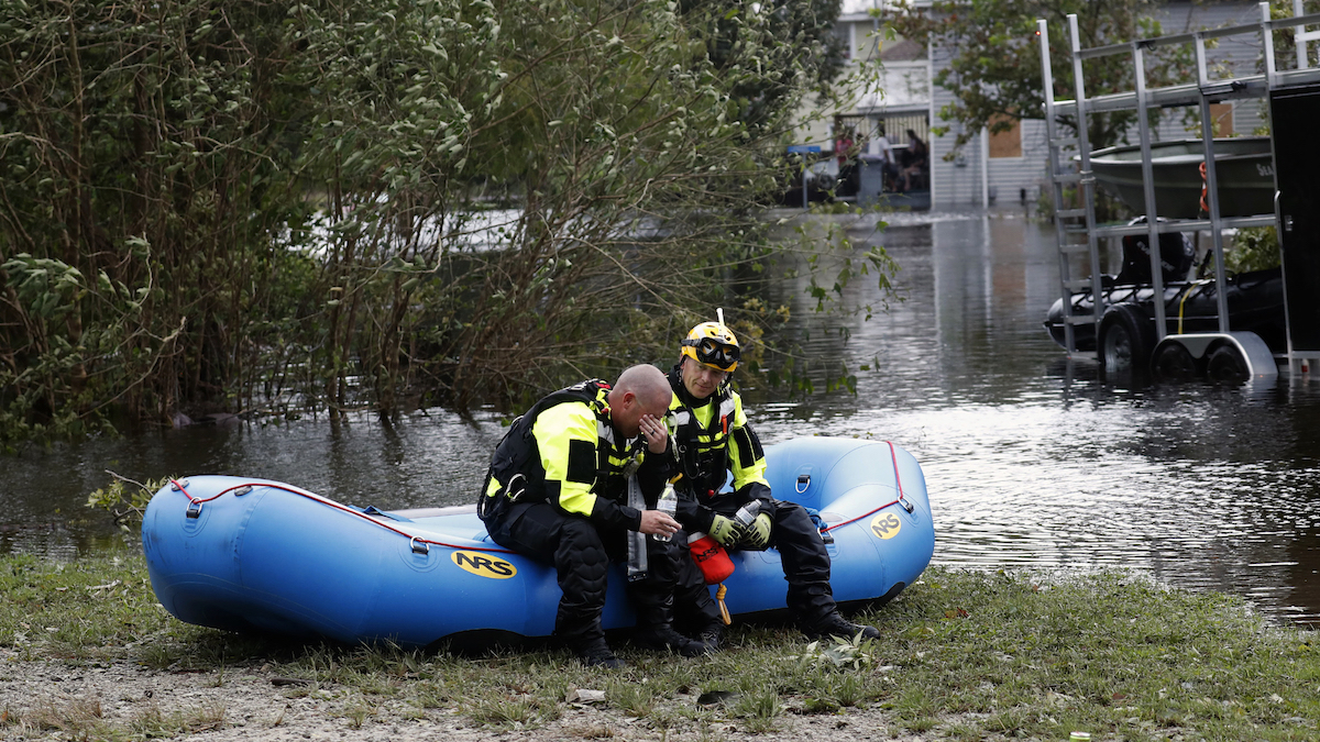 Members of a combined New Bern/Greenville swift water rescue team Brad Johnson, left, and Steve Williams take a rest after they went out searching for people stranded by floodwaters caused by the tropical storm Florence in New Bern, N.C., on Saturday Sept. 15, 2018. (AP Photo/Chris Seward)