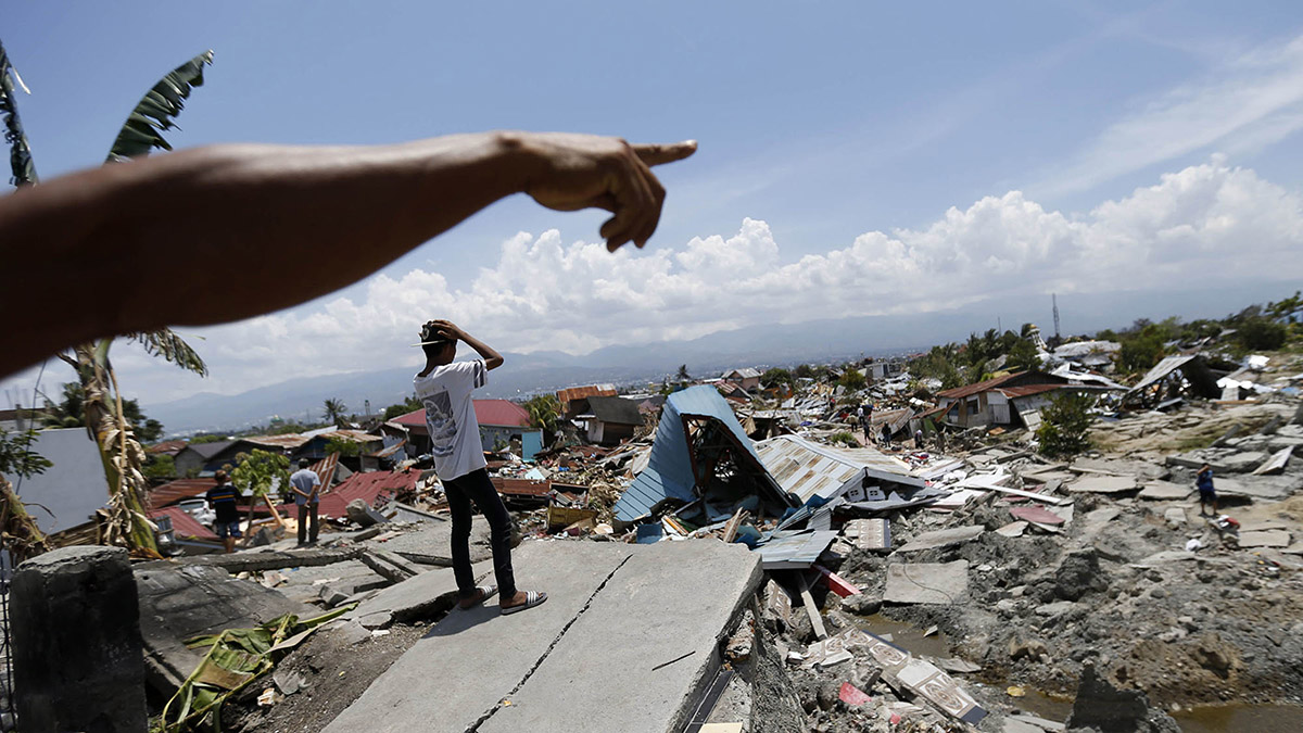 In this file photo, Indonesian men survey the damage in Balaroa neighborhood in Palu, Central Sulawesi, Indonesia, on Tuesday, Oct. 2, 2018.