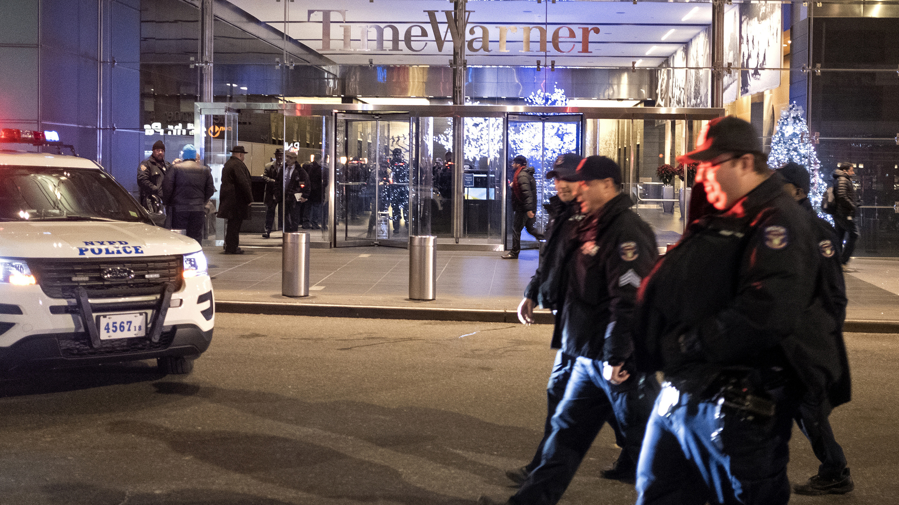 After the building was determined safe, NYPD officers walk from the area of Time Warner Center in New York Thursday night after a bomb threat was called into the building and occupants were evacuated, including CNN employees.