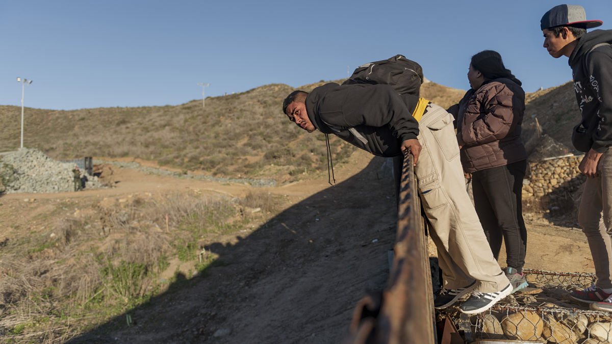 A migrant from Honduras looks from the border fence into the U.S. side before jumping to San Diego, Calif., from Tijuana, Mexico, Thursday, Jan. 3, 2019. Discouraged by the long wait to apply for asylum through official ports of entry, many migrants from recent caravans are choosing to cross the U.S. border wall and hand themselves in to border patrol agents. (AP Photo/Daniel Ochoa de Olza)