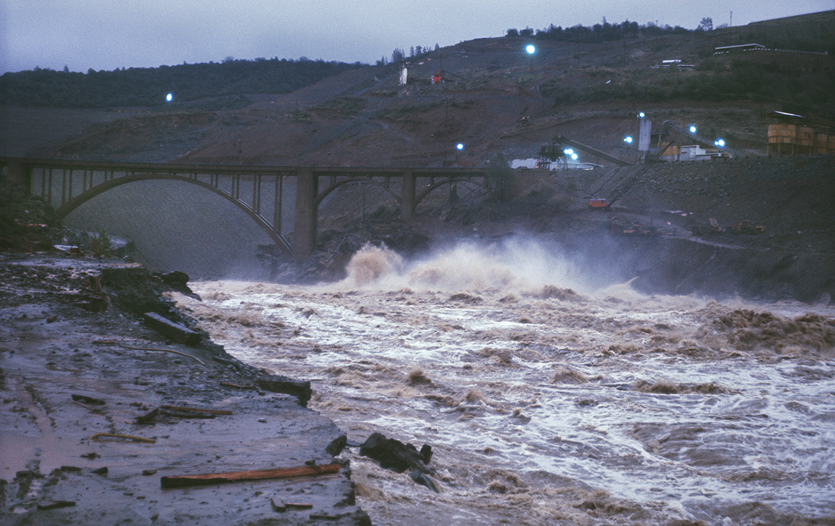 The Oroville Dam embankment was still under construction as flood waters from the Feather River tributaries were discharged in December 1964.
