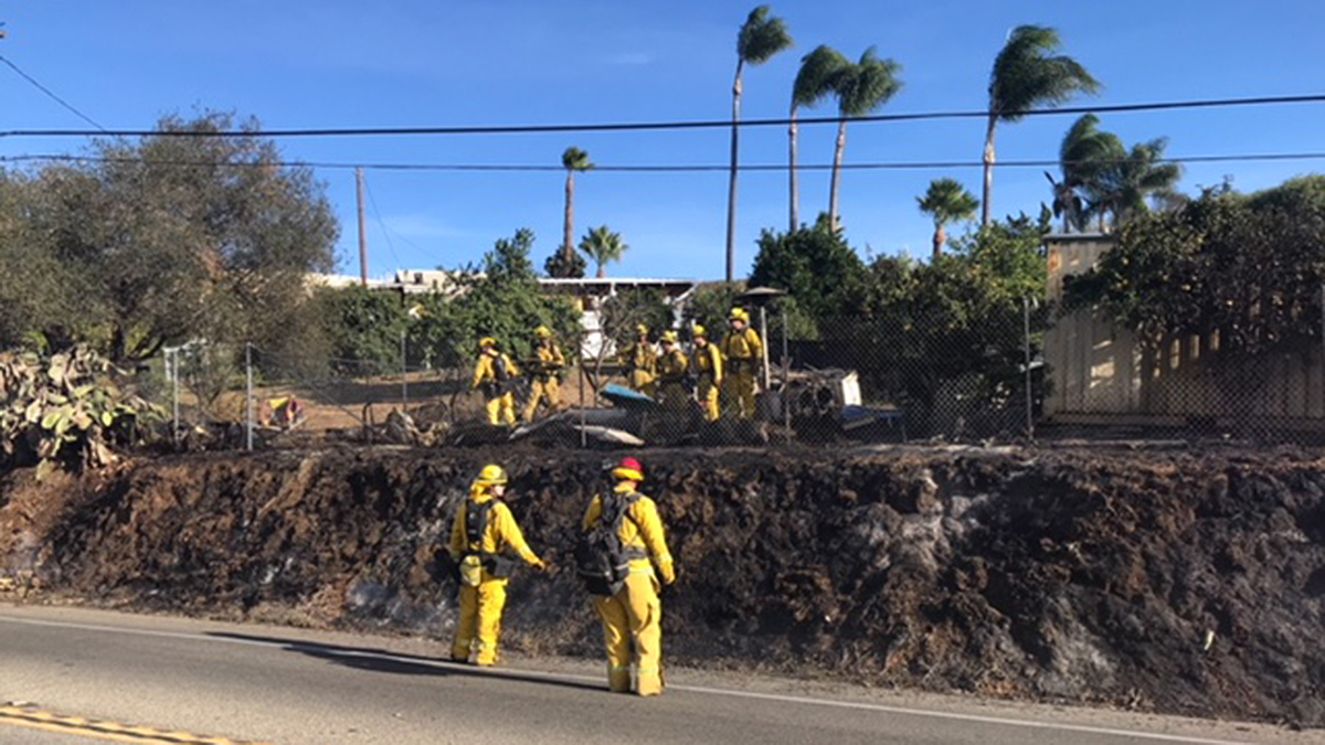 Firefighters clean up after a small brush fire on East Mission Road in Fallbrook on Tuesday, Nov. 13, 2018.
