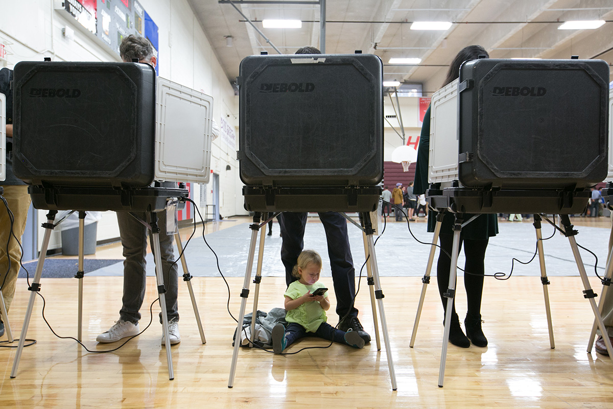Sloane, 2, waits as her father and other voters cast their ballots at a polling station set up at Grady High School for the mid-term elections on Nov. 6, 2018, in Atlanta, Georgia. Georgia has a tight race to elect the state's next governor.