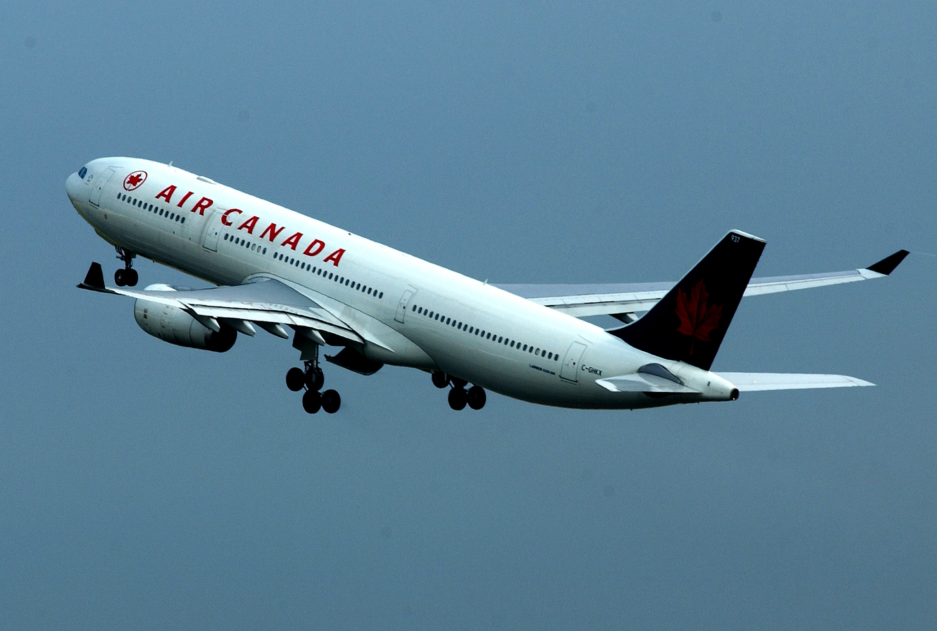 LONDON - JULY 31: An Air Canada passenger plane is shown in flight at Heathrow Airport July 31, 2002 in London, England. Passenger numbers have fallen since the September 11, 2001 terrorist attacks in the United States. Airline companies have all suffered a difficult trading period. (Photo by John Li/Getty Images)